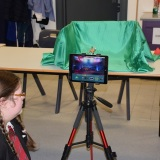 Photograph of a pupil making an animation movie using a school iPad mounted on a tripod and  green  screen background