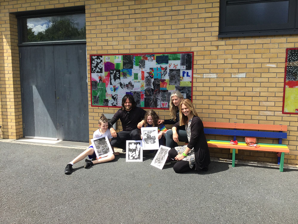 Group picture of the artists, teacher and two pupils in the Primary playground  displaying their  print art work