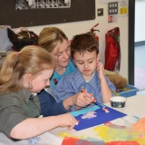 Picture of a staff member assisting two pupils with their  art work
