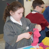 Picture of a pupil cutting a piece of pink material