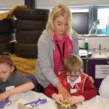 Picture of a pupil cutting out a shape in clay assisted by a staff member