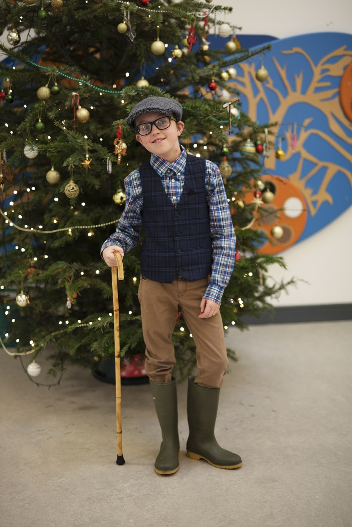 photograph of  a pupil dressed as a shepherd beside the Christmas tree