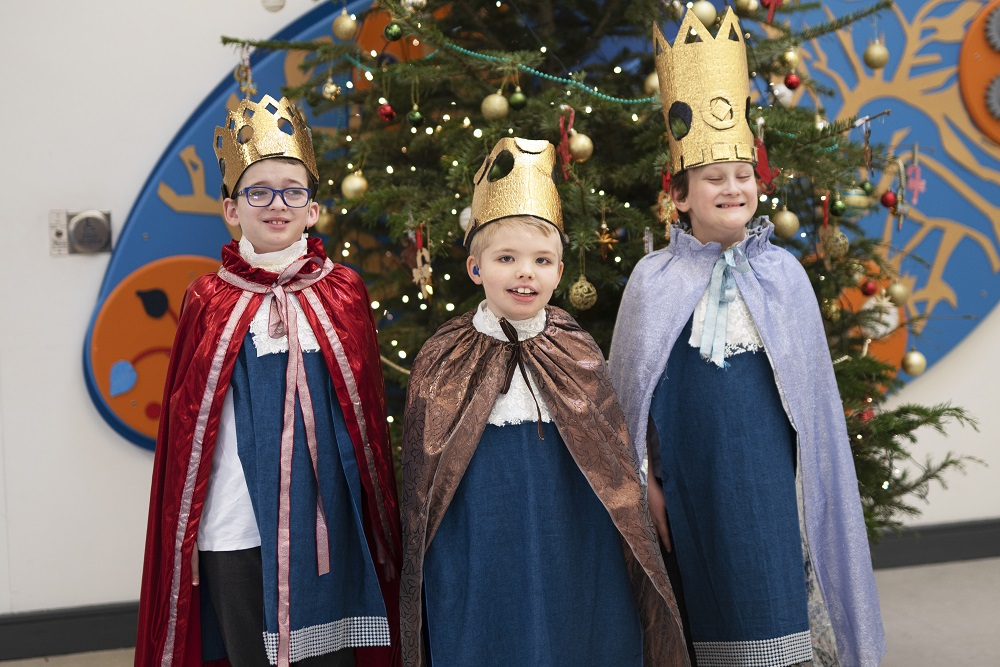 Photograph of  pupils dressed as the three kings beside the Chritsmas tree
