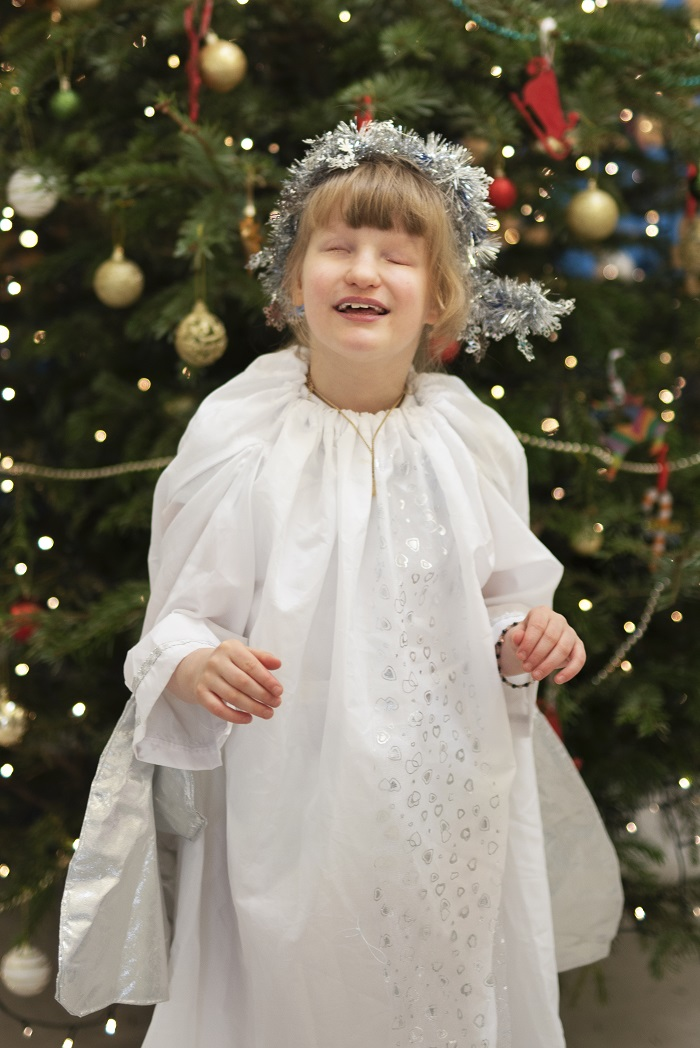 photograph of  a pupil dressed as an angel beside the Christmas tree