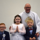 Picture of Father Devlin with the three pupils who received first communion