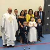 Picture of Father Devlin with the three pupils who received first communion and their families