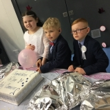 Picture of the three pupils who received first communion cutting the celebration cake