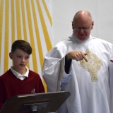 Picture of a pupil reading while Father Devlin signs the words