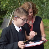 Picture of a teacher and pupil looking at an insect they had found