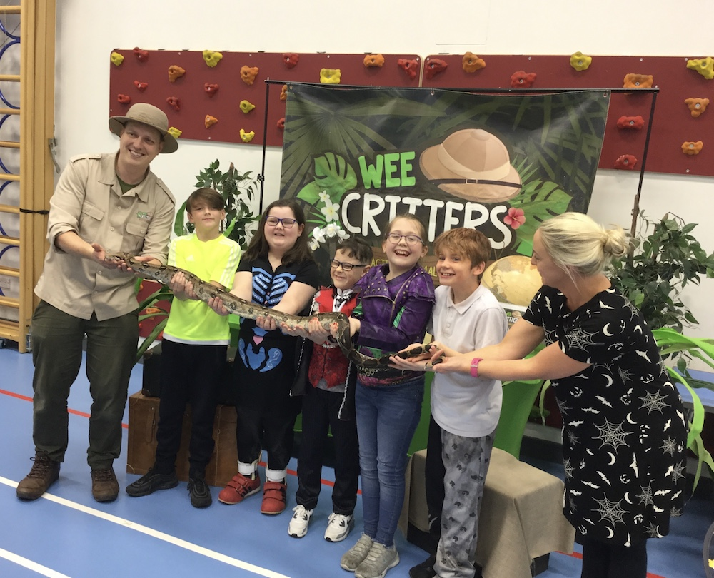 Picture of staff and several  pupils holding a large snake
