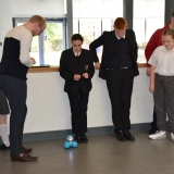 Picture of a teacher and students taken turns to program and move the Dash robot