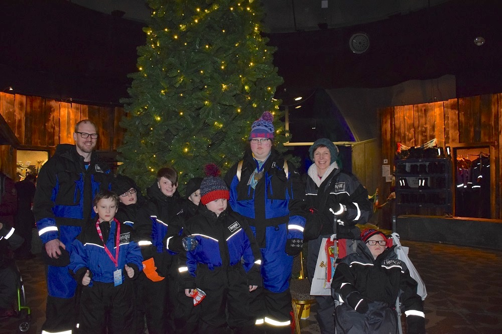 Staff and pupils in front of large Christmas tree