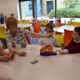 Photograph of a teacher and pupil enjoying a drink and a biscuit during a a game of  Uno