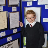 Photograph of pupil pointing at his writing entry