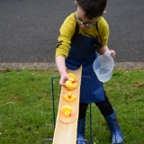 Picture of a pupil playing with a self made wooden  water slide