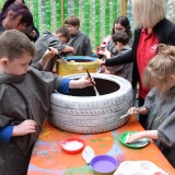 Picture of pupils painting car tyres in the plastic bottle greenhouse