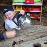 Picture of a pupil outside pretending to pour water from a kettle
