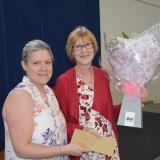 Photograph of a retiring teacher receiving a  bouquet of flowers from a representative  of Jordanstown Together