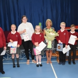 Group photograph of the pupils moving to the secondary department next year after they had presented the special guest  with a bouquet of flowers