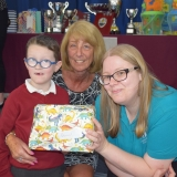 Photograph of a pupil and a teacher after he received his prize from the special guest