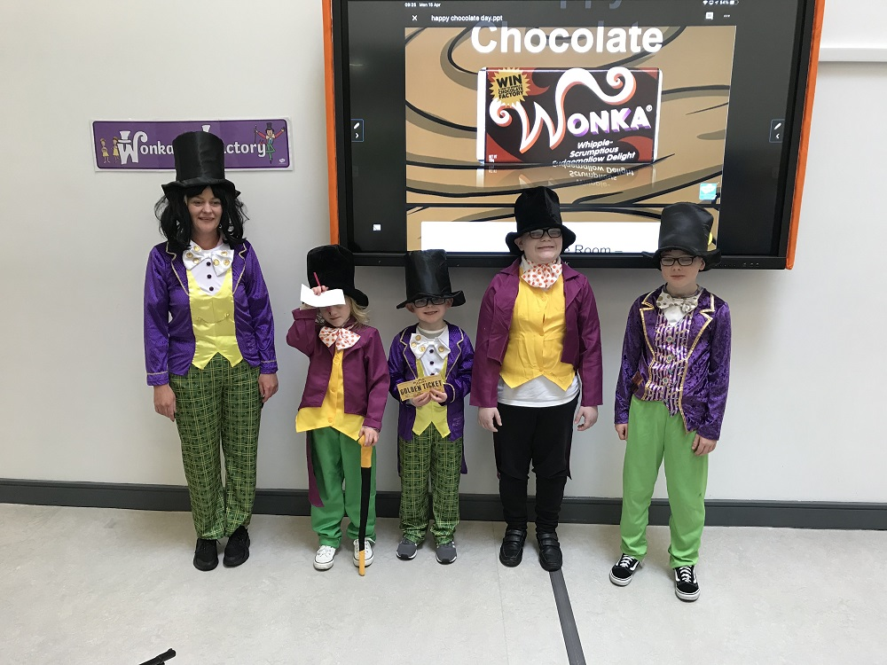 Group picture of a staff member and four pupils all dressed in Willy Wonka costumes