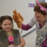 Picture of a teacher using a puppet squirrel with a pupil