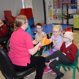 Picture of a teacher, classroom assistants and pupils taking part in a sensory story about Willy Wonka's Chocolate Factory