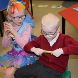 Picture of a two pupils taking part in a sensory story about Willy Wonka's Chocolate Factory