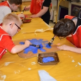 Picture of two pupils painting a cardboard cog for the chocolate machine