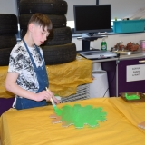 Picture of a pupil painting a cardboard cog for the chocolate machine