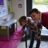 Picture of two pupils using a talking microwave to melt chocolate
