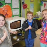 Picture of three pupils using a talking microwave to melt chocolate