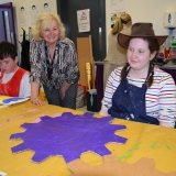Picture of a pupil and classroom assistant with a finished painted blue cog  for the chocolate machine