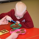 Picture of a pupil filling a plastic mould with chocolate