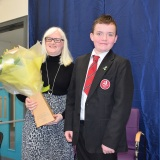 Photograph of Ms Rosaleen Dempsye and a pupil after receiving a bouquet of flowers  form the school