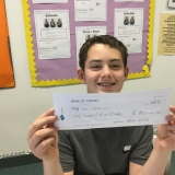 Photograph of a pupil holding the cheque they had written