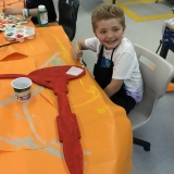 Picture of a pupil painting and decorating the large  wooden outline of a science instrument