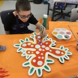 Picture of a pupil painting and decorating the large  wooden outline of a  human cell