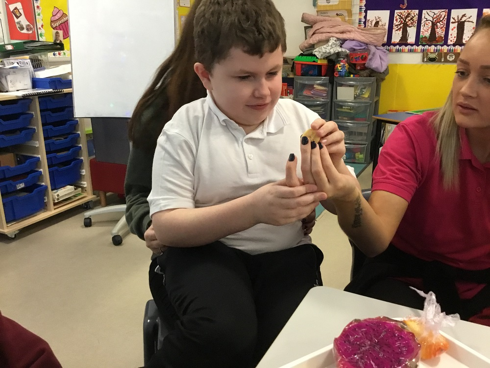 Photograph of a pupil tasting different fruit