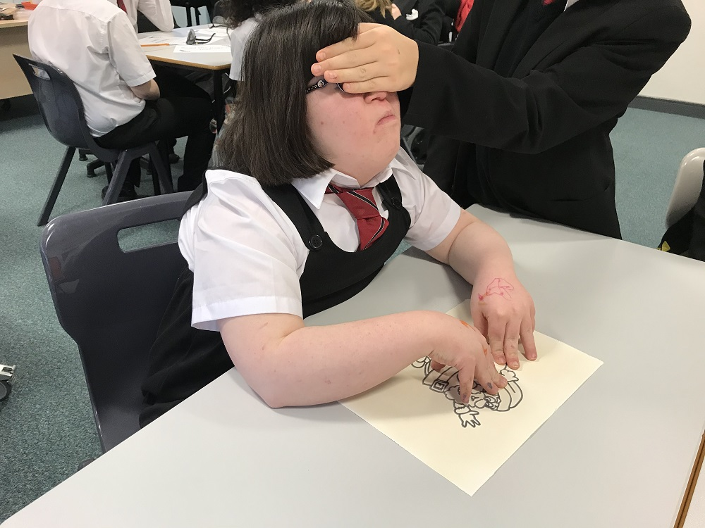 Photograph of a pupil using their fingers to feel a shape on raised paper