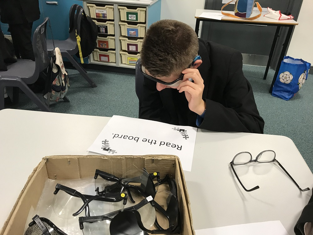 photograph of pupil wearing glasses that simulated being visually impaired while trying to complete a task