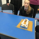 Photograph of pupil testing the strength of bridge made of uncooked spaghetti