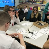 photograph of several pupils wearing glasses that simulated being visually impaired while trying to complete a task