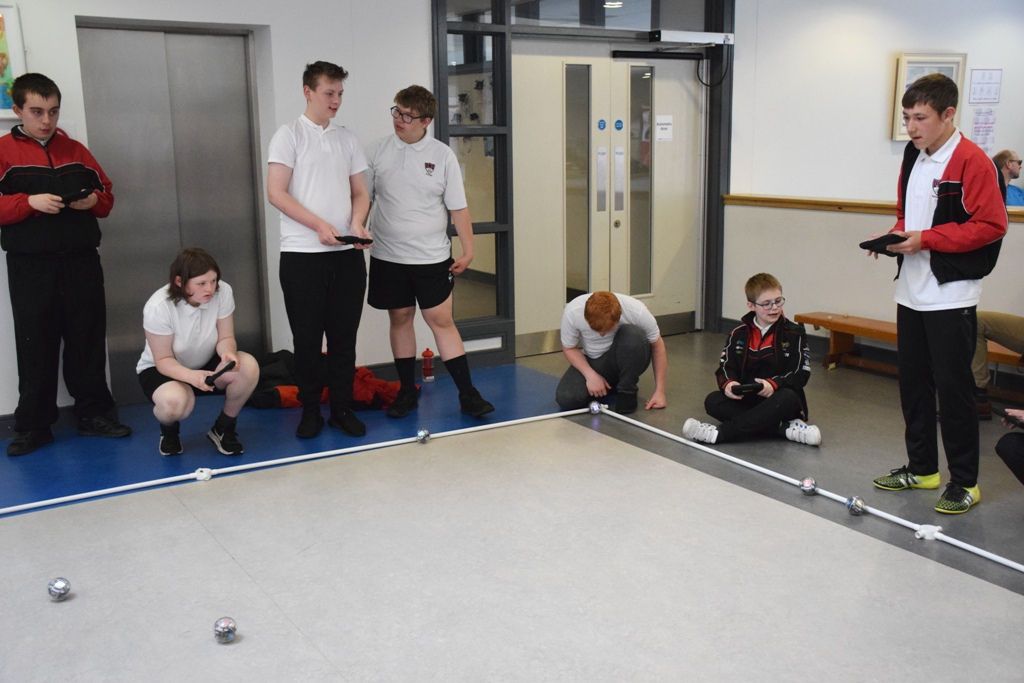 Photograph of  pupils controling   several sphere shaped  robot with iPads
