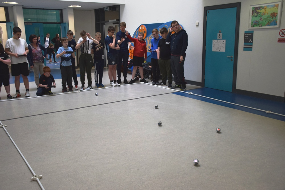 Photograph of  pupils controlling  several sphere shaped  robot with iPads