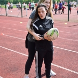Photograph of a pupil with a rugby ball being guided by a staff member