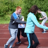 Photograph of a pupil running with a staff member during a game of tag rugby