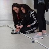 Photograph of a pupil being assisted by a staff member to control a sphere shaped  robot with an iPad