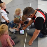 Photograph of a  development officer teaching pupils how to use the iPad to control the sphere shaped robot