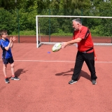 Photograph of a ruby development officer demonstrating to a pupil how to pass a rugby ball